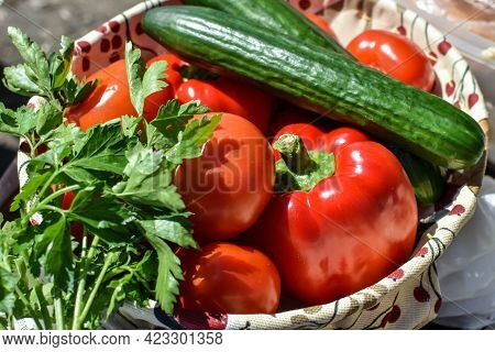Fresh Vegetables On Table On Sunny Summer Day. Tomatoes, Cucumbers And Bell Peppers For Salad Making