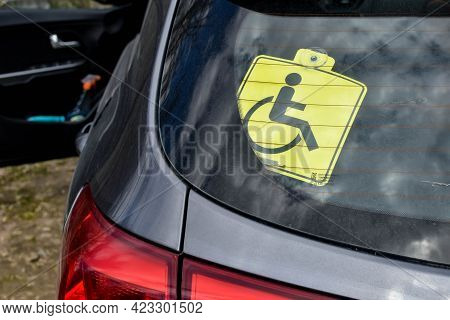 Disability Icon On The Rear Window Of A Car. Identification Symbol Confirming The Right Of Disabled