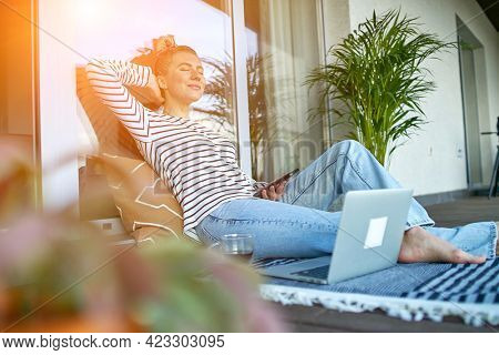 Working from home. Woman talking on video call with Family, using smartphone. Online chat. Spend free time on terrace. Staying connected, Social distancing, internet, chatting.