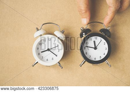 Human's Hand ,black And White Analog Alarm Clock On Grunge Brown Paper Background, Choose The Best T
