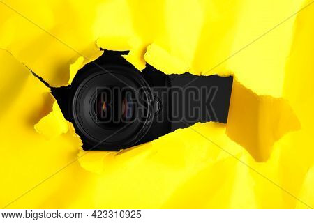 Hidden Camera Spying Through Torn Hole In Yellow Paper, Space For Text