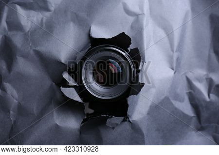 Hidden Camera Spying Through Torn Hole In Black Paper