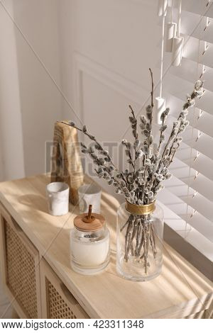 Glass Vase With Pussy Willow Tree Branches And Candle On Wooden Commode Near Window In Room