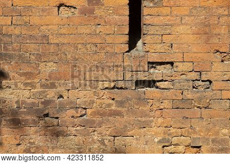 A Loophole In An Old Stone Wall. The Fortification Stone Wall Of An Ancient Castle With Loopholes. B