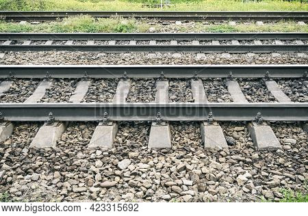 Closeup Of Metal Railway Track With Concrete Railroad Ties On Ballast Stone