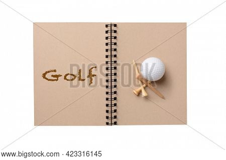 A golf ball and tees on the blank page of a notebook. The opposite page has the word Golf spelled out. Isolated on white.
