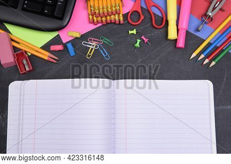 School Supplies: Closeup still life on erased Chalkboard with open notebook and copy space.