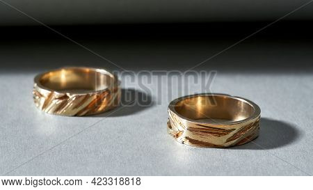 Pair Of Handmade Shiny Jewelry Rings With Embossing Lying On Gray Background, Widescreen. Jewelry Fa