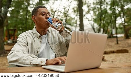 Happy Young African American Man Drinking Energy Drink While Working On Laptop Outdoors, Widescreen.