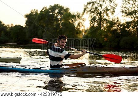 Enthusiastic Young Caucasian Guy Holding A Paddle While Boating On A Lake Surrounded By Nature. Kaya