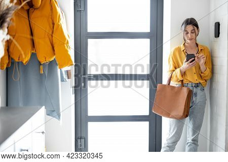 Young Businesswoman In Casual Standing With Phone And Bag At The Hallway, Putting House On Alarm By