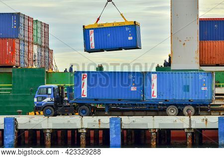 Labuan,malaysia-may 20,2021:busy Crane Operator Unloading The Container From A Cargo Ship In The Por