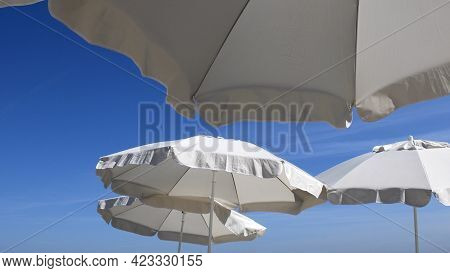Fluttering Frills Of White Textile Umbrellas Against Blue Sky Background With Copy Space. Beach Para