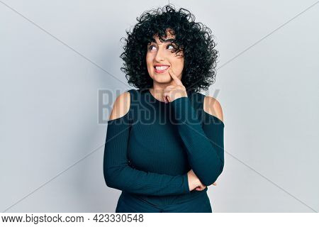 Young middle east woman wearing casual clothes thinking concentrated about doubt with finger on chin and looking up wondering