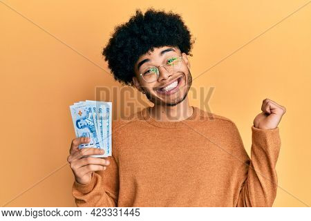 Young african american man with afro hair holding 50 thai baht banknotes screaming proud, celebrating victory and success very excited with raised arm