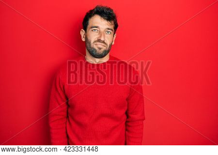 Handsome man with beard wearing casual red sweater looking sleepy and tired, exhausted for fatigue and hangover, lazy eyes in the morning.