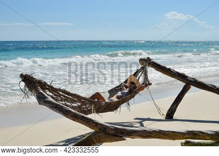 A Woman In A Swimsuit Sunbathes In A Hammock On A Tropical Beach. Picturesque Exotic Landscape. Sunb