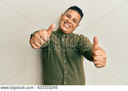 Young latin man wearing casual clothes approving doing positive gesture with hand, thumbs up smiling and happy for success. winner gesture.