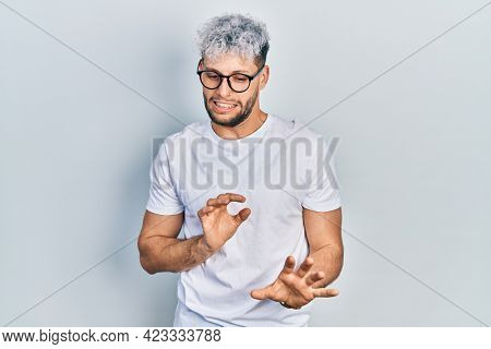 Young hispanic man with modern dyed hair wearing white t shirt and glasses disgusted expression, displeased and fearful doing disgust face because aversion reaction.