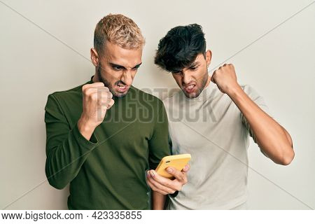 Homosexual gay couple standing together using smartphone annoyed and frustrated shouting with anger, yelling crazy with anger and hand raised