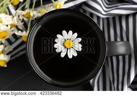 Chamomile Tea With Kitchen Towel And Chamomile In Gray Ceramic Cup On The Black Cement Table. Herbal