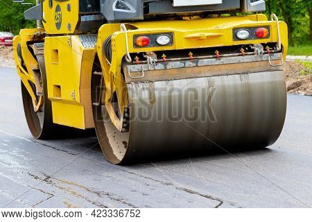 Asphalt Paver On The Road During Asphalt Compaction Close Up. Road Repair. Laying A New Road