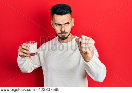 Young hispanic man with beard holding glass of milk annoyed and frustrated shouting with anger, yelling crazy with anger and hand raised