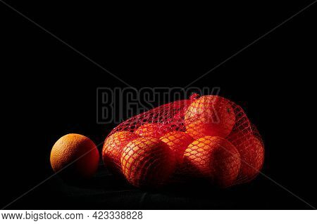 Ripe Oranges In A Mesh Bag On A Black Background.