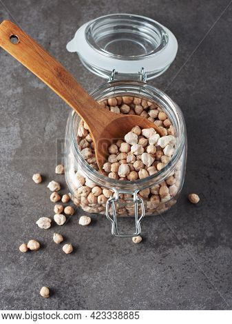 Dry Chickpeas In A Jar With A Wooden Spoon On A Dark Background.