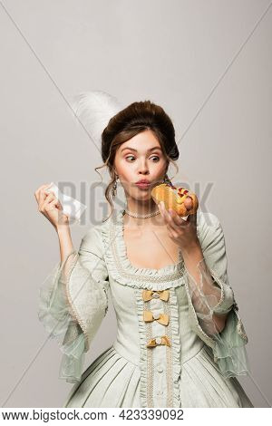 Astonished, Vintage Style Woman Holding Hot Dog And Paper Napkin Isolated On Grey