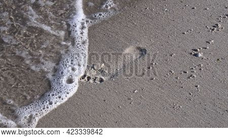 Sea Foam Surf At Clean White Sand With Footprint Of Barefoot Legs. Waves Erase Footprint From Beach