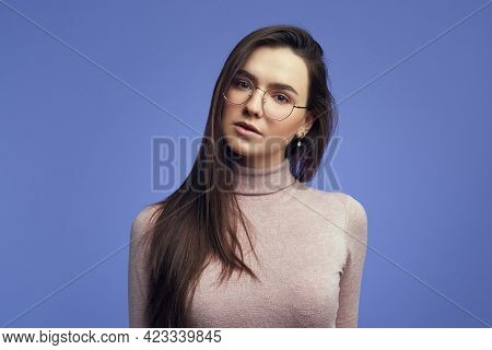 Girl Looks Seriously At Camera, Wears Round Spectacles Against Violet Wall