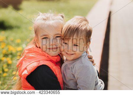 Older Sister Hugs Her Little Brother In Summer In The Park
