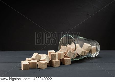 Scattered Wooden Cubes From A Glass Beaker On A Dark Surface. Overflow Concept