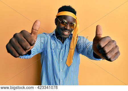 Handsome black man drunk wearing tie over head and sunglasses approving doing positive gesture with hand, thumbs up smiling and happy for success. winner gesture.