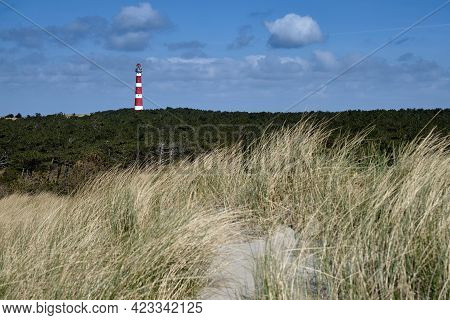 Classic, Historic Old Red And White Lighthouse With Dunes And Grass, Sunny Windy Day And Turbulent C