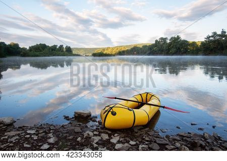 Yellow packraft rubber boat with red padle on a sunrise river. Packrafting. Active lifestile concept