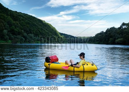 Tourist on yellow packraft rubber boat with red padle on a sunrise river. Packrafting. Active lifestile concept