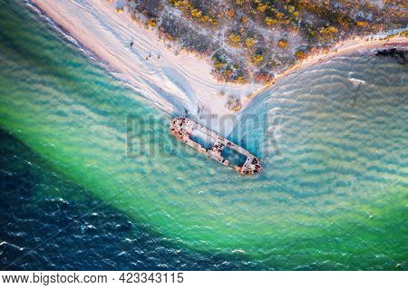 Old shipwreck reinforced concrete barge abandoned stand on beach on the coast of Black sea in Ukraine