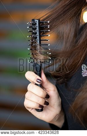 The Girl Is Combing Her Long Red Hair With A Massage Comb.