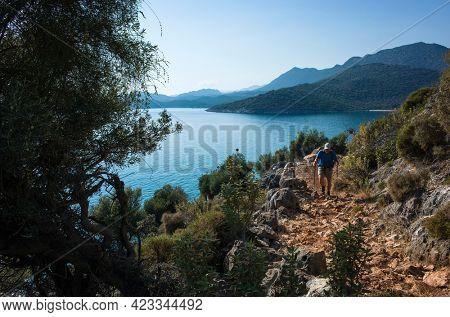 Hiking Lycian way. Man is trekking on stony path along Mediterranean sea coast on Lycian Way trail from Ucagiz to Demre, Outdoor activity in Turkey