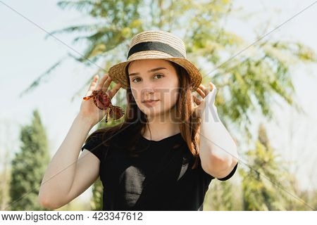 A Beautiful Young Girl In A Straw Hat And With Sunglasses In Her Hands. Portrait Of A Stylish Girl