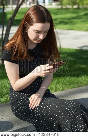 A Young Beautiful Girl With Long Hair And Wearing A Black T-shirt And Skirt Is Sitting On Street Wit