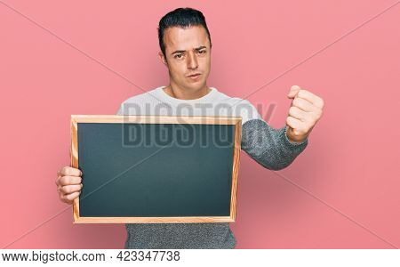 Handsome young man holding blackboard annoyed and frustrated shouting with anger, yelling crazy with anger and hand raised