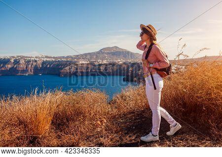 Traveler Woman Walking On Santorini Island, Greece Enjoying Landscape. Happy Girl With Backpack Enjo