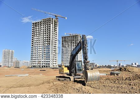 Excavator On Earthmoving At Construction Site. Backhoe Digs Sand On Blue Sky Background. Constructio