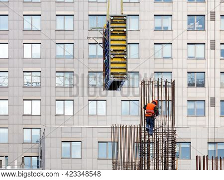 A Builder In A Bright Orange Vest And A Safety Helmet At A Height Mounts The Formwork On A Metal Fra