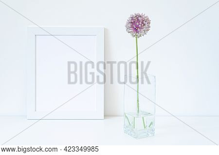 Empty White Picture Frame Mockup. Glass Vase With Allium Ampeloprasum Flower Over White Table With W