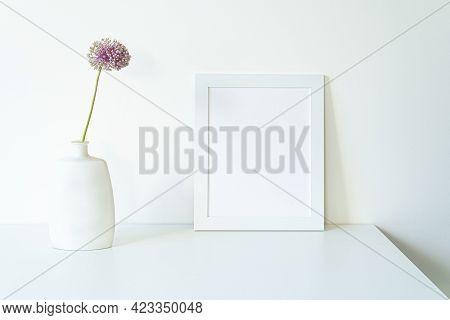 Empty White Picture Frame Mockup. Modern And Elegant Vase With Allium Ampeloprasum Flower Over White
