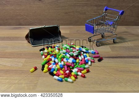 Pills With Wallet At A Shopping Basket On Wood Backgrond. Economy Concept Of Spending Money On Medic